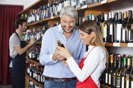 saleswoman: Happy mature customer and saleswoman looking at red wine bottle in shop