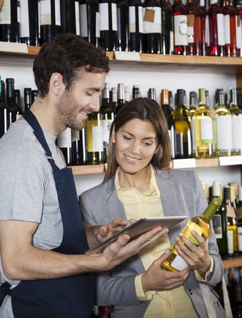 store keeper: Young salesman showing wine information to female customer on digital tablet in supermarket Stock Photo