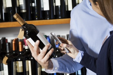 purchases: Midsection of couple scanning barcode on wine bottle through smartphone in supermarket