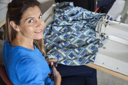 angle: High angle portrait of confident female tailor cutting fabric at workbench in sewing factory