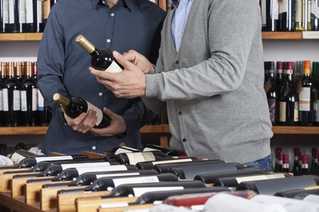 Midsection of male friends holding wine bottles at table rack in shop Foto de archivo