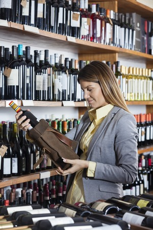 mid adult   female: Mid adult female customer removing wine bottle from bag in store