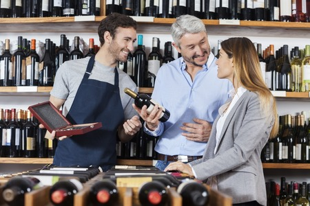store keeper: Happy mature man holding wine bottle while standing with woman and salesman in shop