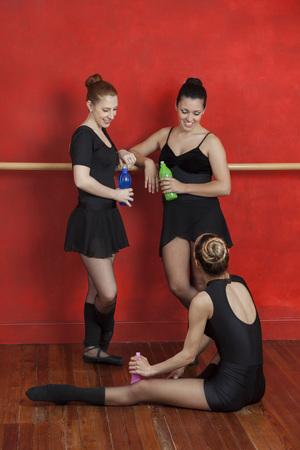 ballet bar: Full length of happy ballerinas with water bottles in dance studio