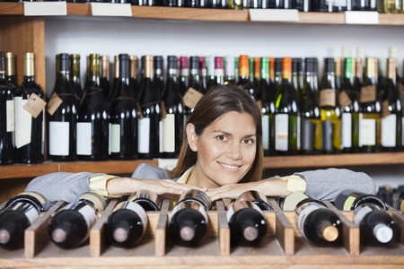 store keeper: Portrait of confident female customer leaning on wine rack in shop