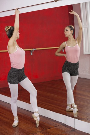 full length mirror: Full length of young ballerina performing while looking at self in mirror