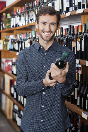 store keeper: Portrait of smiling young male customer holding wine bottle by shelves in store Stock Photo