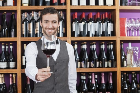 store keeper: Portrait of confident bartender offering red wine glass against shelves in winery