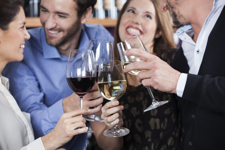 toasting wine: Happy male and female friends toasting wine glasses at shop Stock Photo