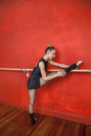 dance bar: Full length of young ballerina with leg on bar performing in dance studio