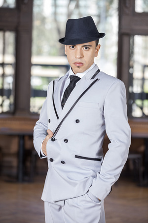 argentina dance: Portrait of confident tango dancer with hand in jacket performing at restaurant