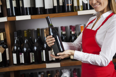 alcohols: Midsection of smiling saleswoman holding wine bottle in supermarket