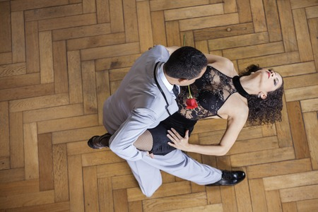 sensuous: High angle view of sensuous young woman performing tango with partner on hardwood floor at restaurant