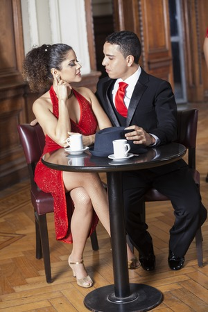 argentina dance: Full length of tango couple sitting at table in restaurant Stock Photo