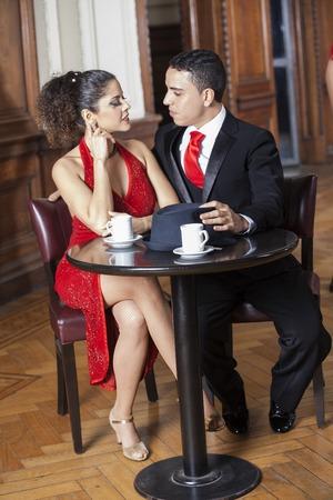 parejas enamoradas: Toda la longitud de pareja de tango sentado a la mesa en el restaurante Foto de archivo