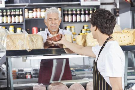 Felice venditore anziano riceve formaggi collega in negozio di alimentari photo