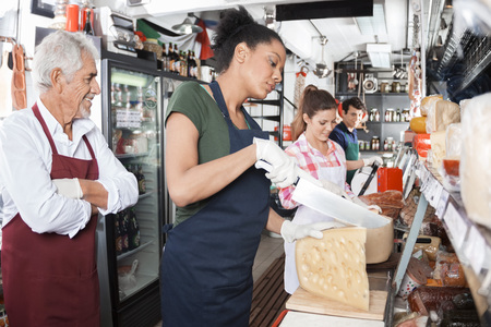 food shop: Happy owner looking at workers cutting cheese at counter in shop Stock Photo