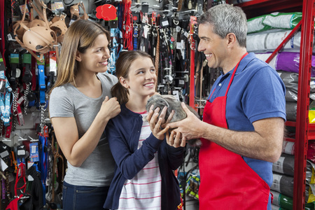petshop: Happy salesman giving rabbit to girl with mother at pet store Stock Photo