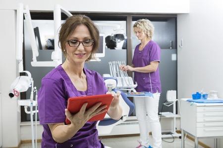 comunicacion oral: asistente de la mujer que usa la tableta digital mientras colega que trabaja en la odontolog�a Foto de archivo