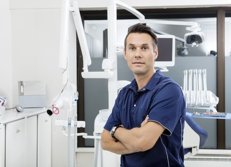 Portrait of confident dentist with arms crossed at clinic Stock Photo