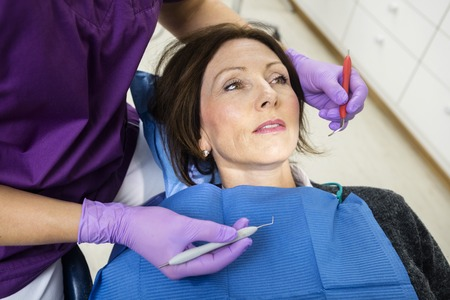 scaler: High angle view of dentist examining patient with tools in clinic Stock Photo