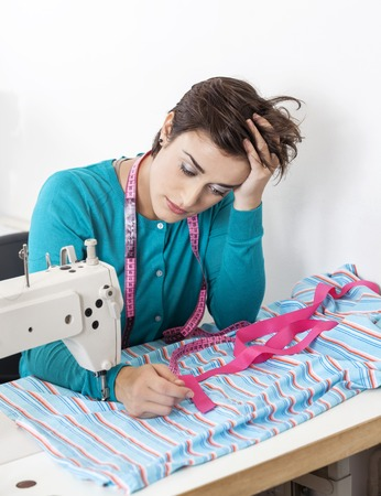 modiste: Stressed female tailor leaning on workbench in sewing factory