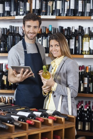 shop keeper: Portrait of salesman holding digital tablet while female customer with wine bottle in shop