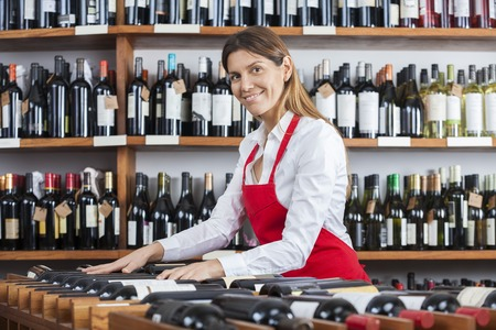 saleswoman: Portrait of mid adult saleswoman arranging wine bottles in rack at shop