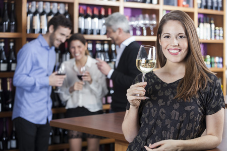shop keeper: Portrait of happy young woman holding wineglass with friends in background at shop