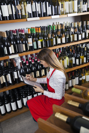 Mid adult saleswoman taking inventory in wine store