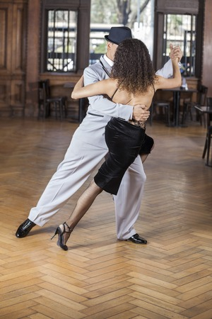 argentina dance: Full length of male and female dancers performing tango in restaurant Stock Photo