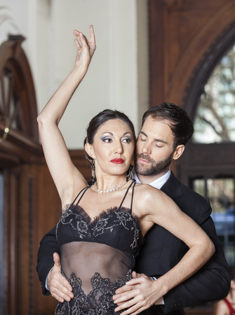 sensuous: Sensuous mid adult man and woman performing tango dance in restaurant