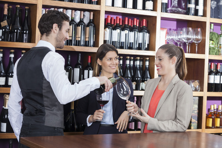 store keeper: Smiling bartender serving red wine to female customers at shop