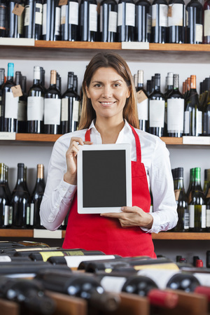 store keeper: Portrait of confident saleswoman showing blank digital tablet in wine shop