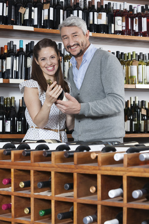 copule: Portrait of smiling couple with wine bottle standing at rack in shop Stock Photo