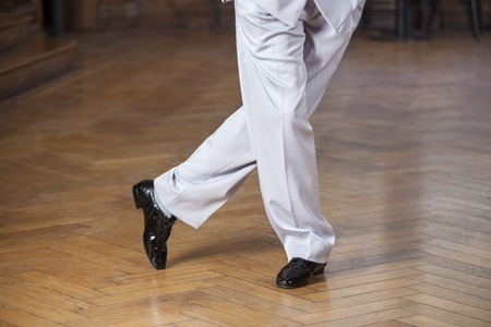 argentina dance: Low section of male dancer performing tango on hardwood floor at restaurant Stock Photo