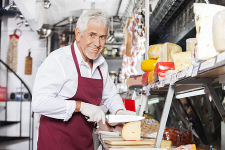slicing: Portrait of happy salesman slicing cheese at counter in shop Stock Photo