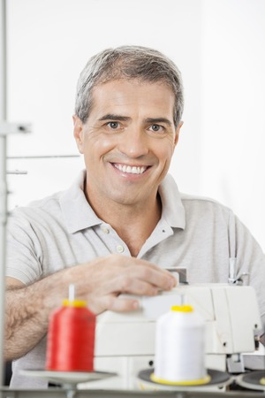 modiste: Portrait of happy mature male tailor adjusting sewing machine in factory