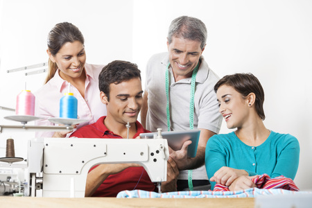 modiste: Team of smiling tailors using tablet computer at workbench in sewing factory