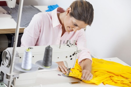 modiste: Smiling female tailor stitching yellow fabric at workbench in factory Stock Photo