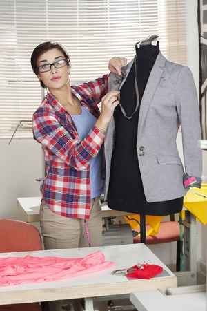 pinning: Confident female fashion designer pinning suit on mannequin at sewing factory