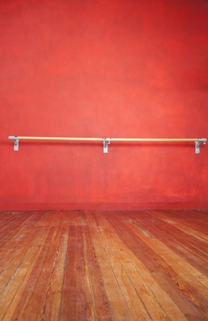 barre: Ballet bar against red wall in dance studio Stock Photo