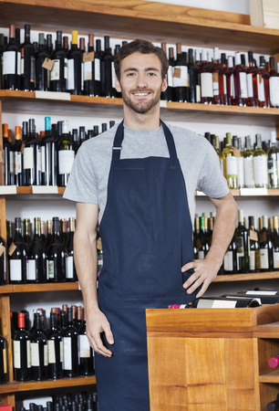 shop keeper: Portrait of confident young salesman standing in wine shop