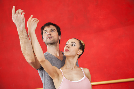 male ballet dancer: Young female ballet dancer performing with male trainer against red wall at studio Stock Photo