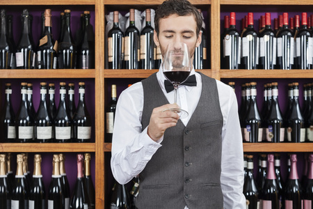 store keeper: Young bartender smelling red wine against shelves in winery