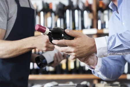 store keeper: Midsection of male customer and salesman with wine bottles in shop