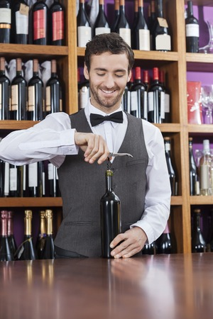 shop keeper: Smiling bartender using corkscrew to open wine bottle at counter in winery Stock Photo