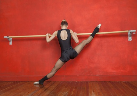 ballet bar: Full length rear view of young ballerina practicing at ballet studio