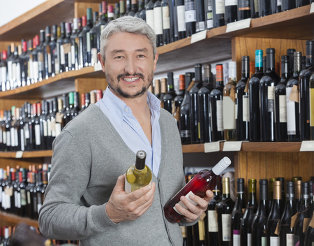 liquors: Portrait of happy mature customer holding red and white wine bottles in store