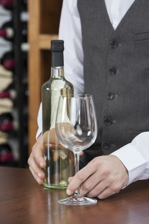 store keeper: Midsection of bartender with white wine and glass at counter Stock Photo
